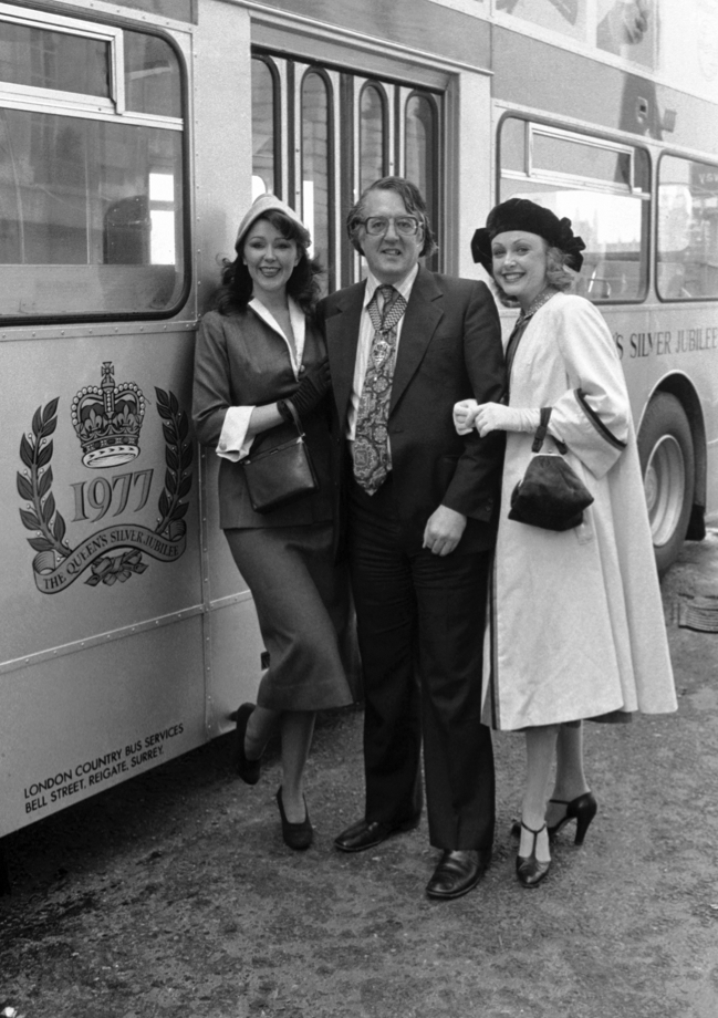 GLC Chairman Lord Ponsonby is flanked by models Lina Hooks, left, and Jan Emery - both dressed in the attire of 1952 - as he introduces the first of 50 silver buses celebrating the silver jubilee